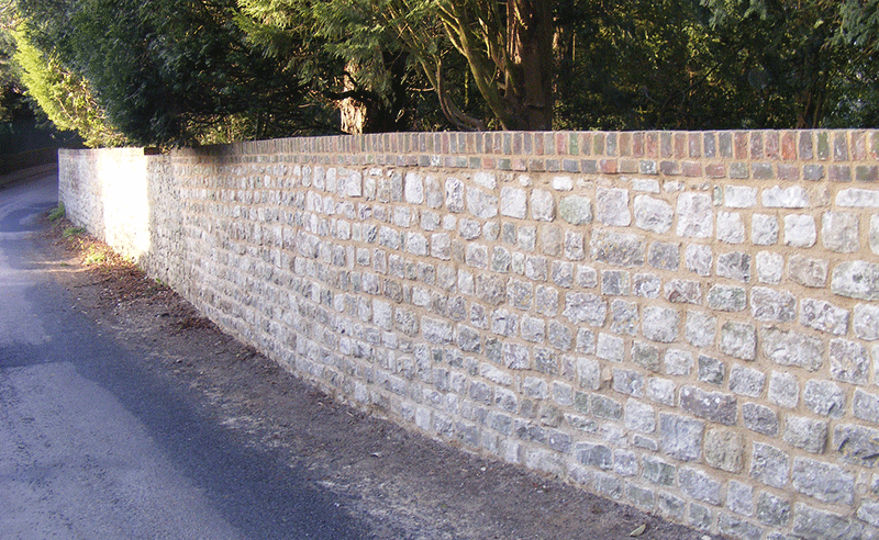 Boundary wall built with dressed stone & lime mortar