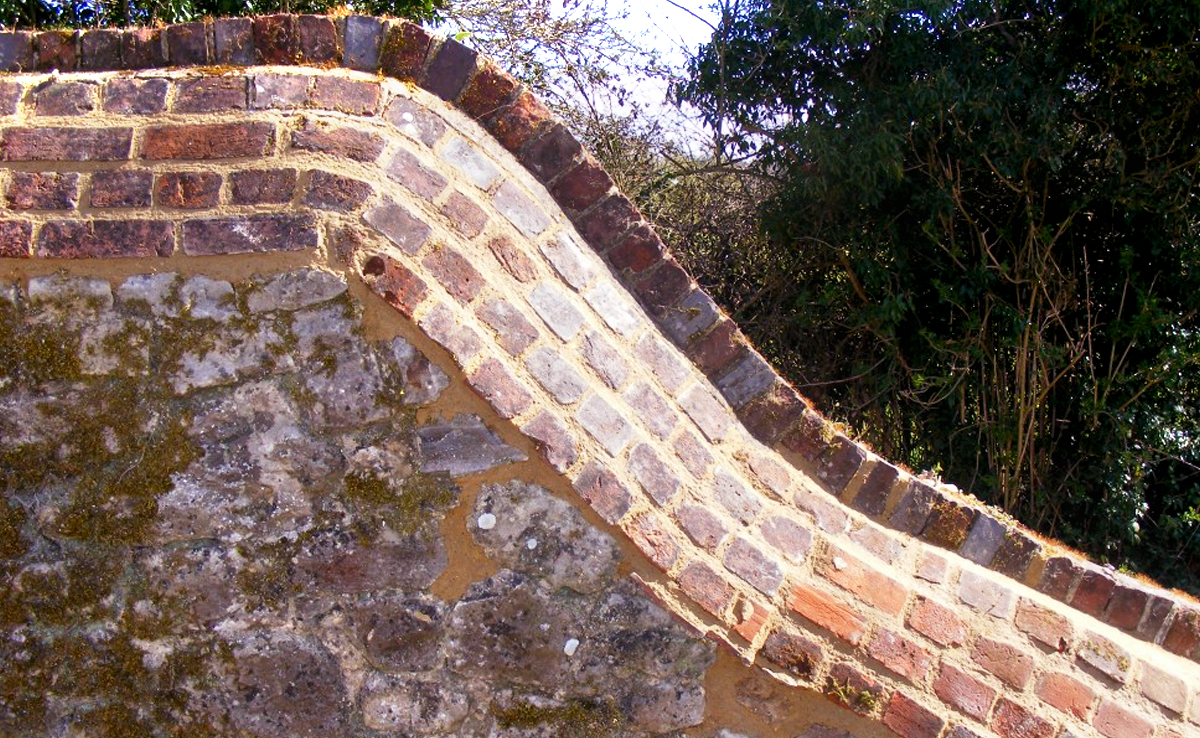 REpair to a weather damaged brick and ragstone boundary wall