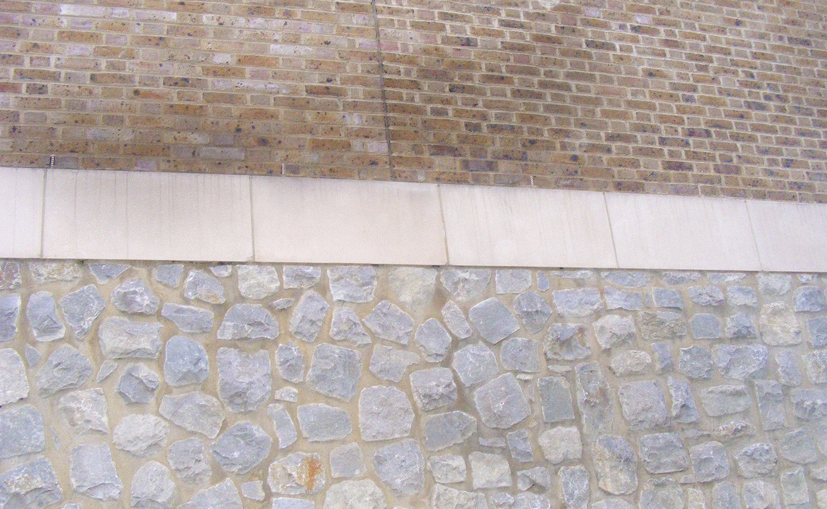 Wall constructed with a mix of ragstone, limestone and traditional brick